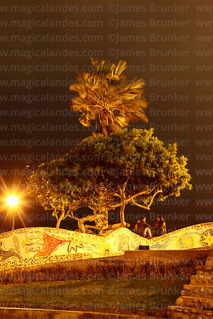 Couple sitting on wall in Parque del Amor / PArk of Love at night, Miraflores, Lima, Peru