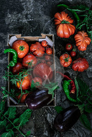 Tomatoes and vegetables on a dark background