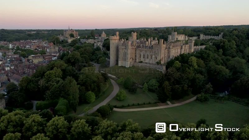 Drone moves slowly towards Arundel Castle and town in the light of a summer dawn