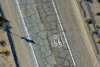 A route 66 road sign on the cracked pavement of Route 66 near Amboy,  San Bernardino County, California, USA.