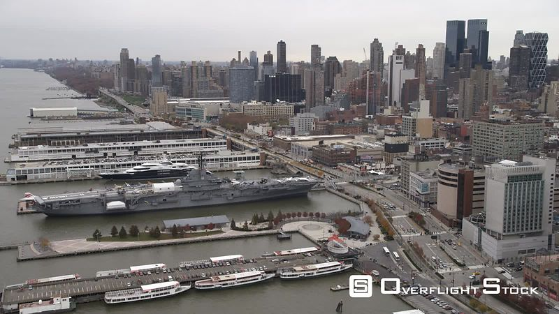 Flying over the Hudson past Midtown Manhattan, naval carrier USS Intrepid at dock.