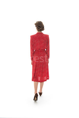 A 1940's woman in a red dress, walking away – shot from eye-level.