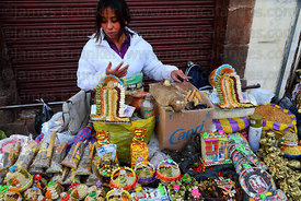 Woman selling a variety of lucky charms in market for Alasitas festival, Puno, Peru
