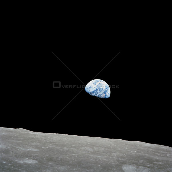 24 Dec. 1968) --- The rising Earth is about five degrees above the lunar horizon in this telephoto view taken from the Apollo 8 spacecraft near 110 degrees east longitude.