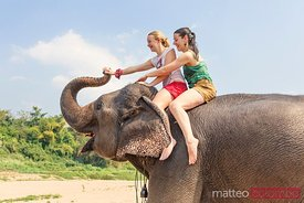 Laos, Luang Prabang. European tourists riding an elephant
