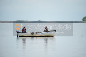 A fisherman plays a trout from a boat on Rutland Water