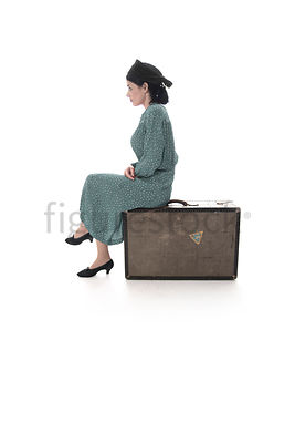 A 1940's woman in a hat, sitting on a suitcase – shot from mid-level.