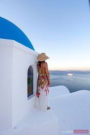Woman looking at mediterranean sea from blue domed church in Santorini