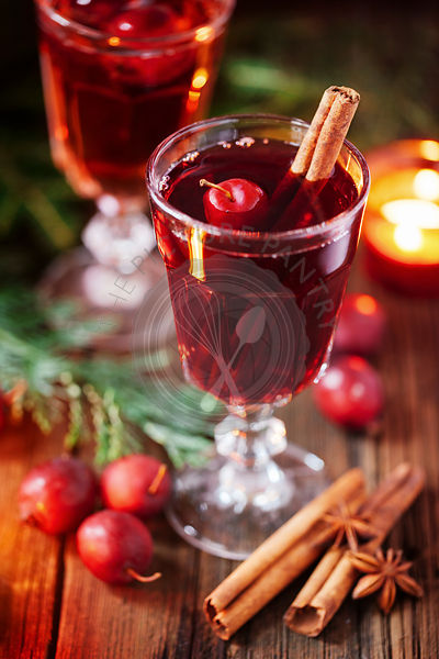 Hot mulled wine with small crab apples, cinnamon stick ans anise closeup