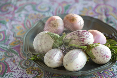 plated white aubergines with purple fine stripes and onion against purple floral tablecloth, text space,
