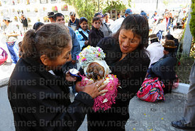 Woman rubbing Nivea cream on skull to protect it from the sun! Ñatitas festival, La Paz, Bolivia