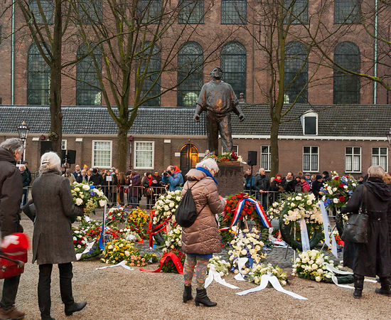 People and flowers surround the statue of the Dokworker