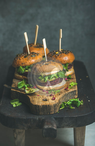 Healthy homemade vegan burger with beetroot-quinoa patty on wooden table