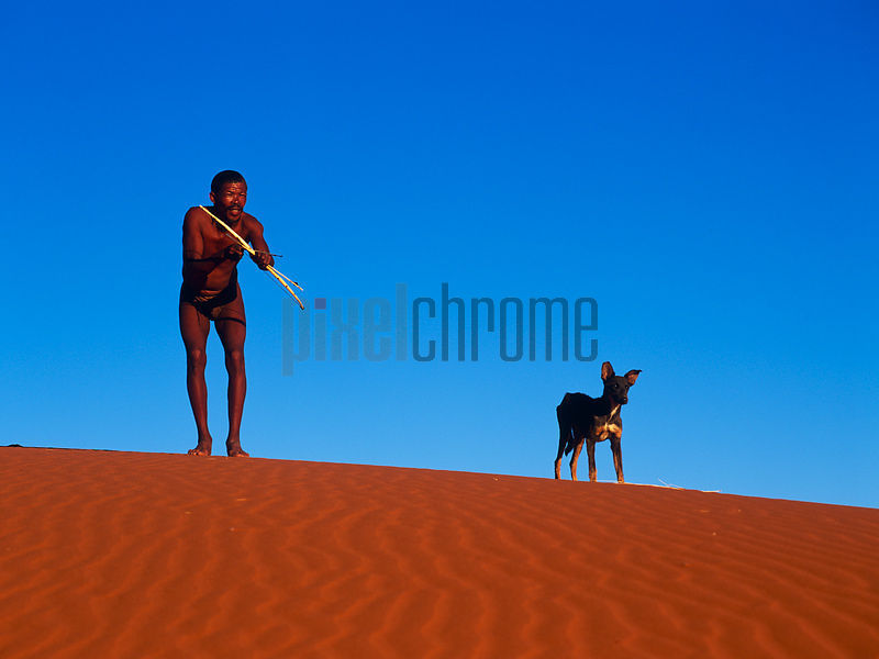 San Hunter Standing on a Sand Dune with Dog