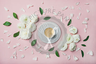 Cup of coffee surrounded with white ranunculus flowers and petals over light pink pastel background