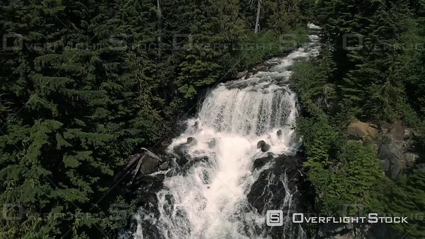 Aerial flowing down stream panning over cascading waterfalls in Canada