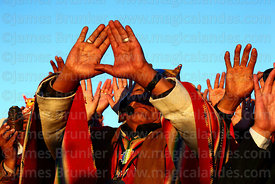 An Aymara shaman or amauta holds up his hands to receive the sun's energy at sunrise during Aymara New Year celebrations, Tiwanaku, Bolivia