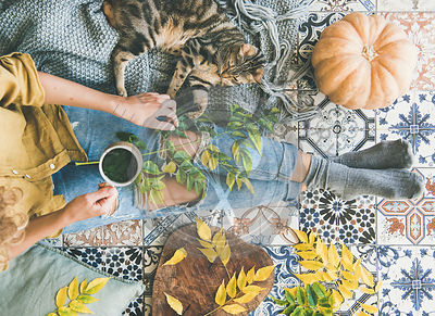 Woman sitting on floor with cat and drinking autumn tea
