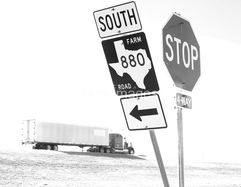 Semi-truck with Texas farm road sign and stop sign in the foreground