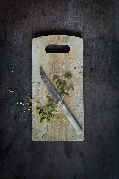Whole and chopped pistachios with vintage knife on rustic wooden board on wooden table top. Top view