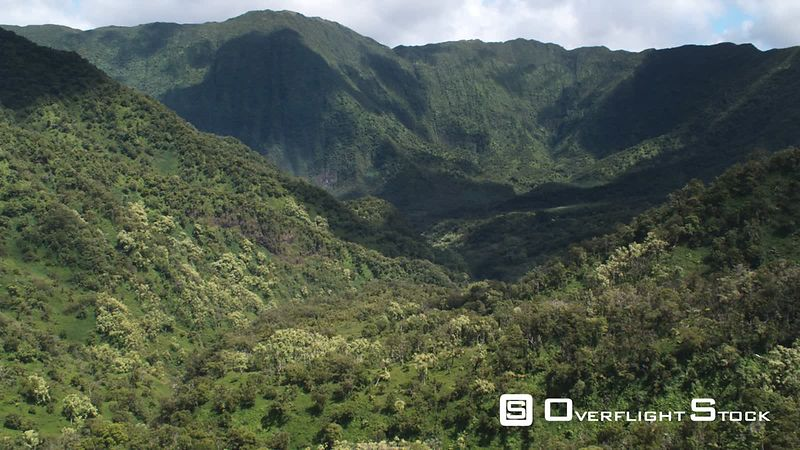 Flying through tree-covered valley toward cloud-dappled mountains, Molokai.