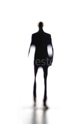 A silhouette of an abstract blurred man walking away – shot from mid level.