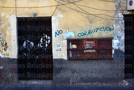 No corruption graffiti and advert offering to buy long hair hair on wooden shutter, La Paz, Bolivia