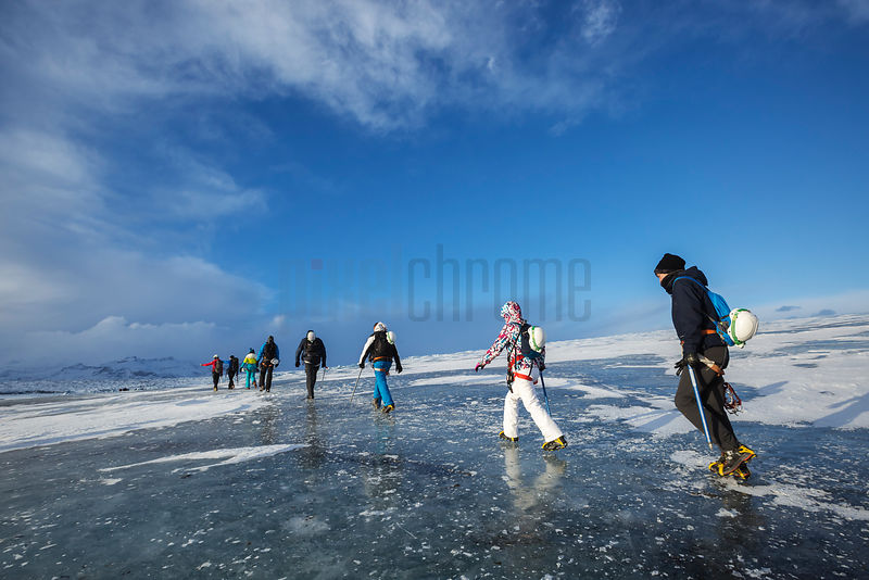 Group of Ice Tourists Hiking Across a Glacier