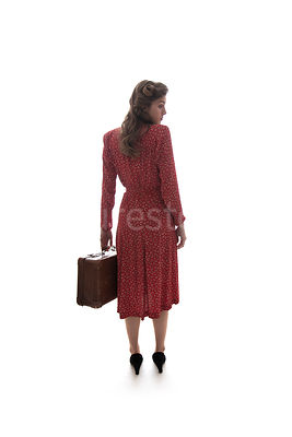 A 1940's woman in a red dress, standing with a suitcase – shot from eye-level.