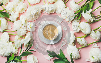 Flat-lay of cup of coffee surrounded with white ranunculus flowers over light pink pastel background