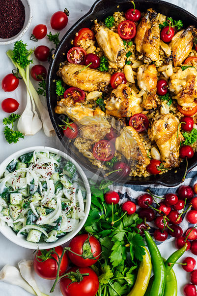 Chicken wings and bulgur pilaf cooked in one pan, garnished with cherries, cherry tomatoes and herbs photographed from top view.