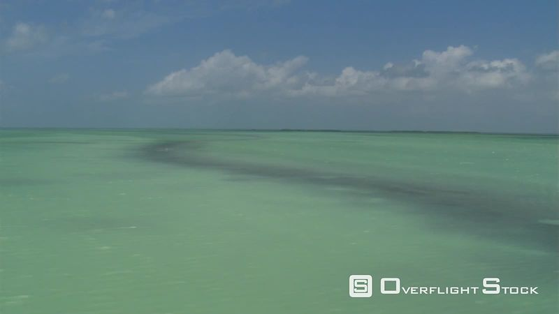 Flight over sunny green Atlantic waters off the Florida coast, passenger POV