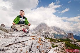 Child meditating on top of the mountains in summer