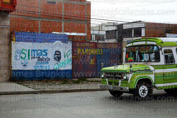 Local public bus called a micro driving past slogans on wall showing support for Movimiento al Socialismo MAS political party, El Alto, Bolivia