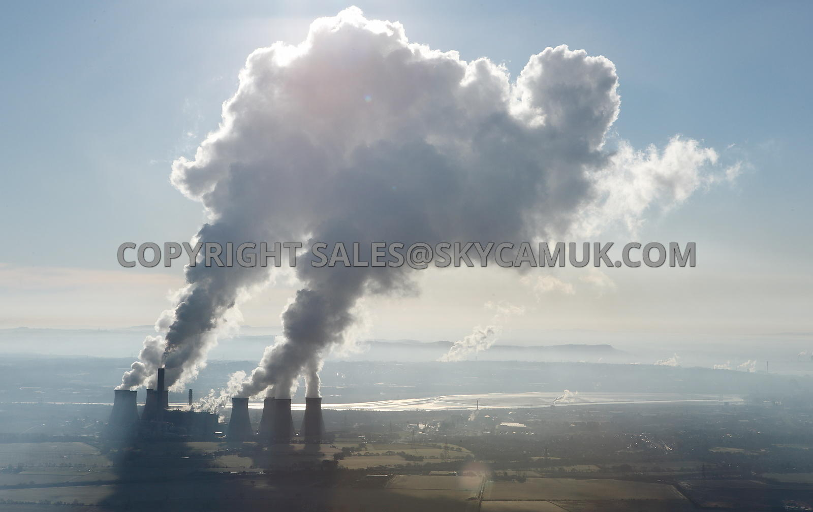 Fiddlers Ferry Power Station a dramatic aerial photograph of the clouds of steam being backlighted by the angle of the sun outlining the shape of the rising plumes of steam against a blue sky and the reflection on the river Mersey