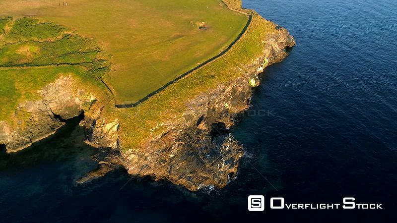 Drone camera looks down at stunning cliffs and headland in Cornwall. Shot with the golden light of dawn.