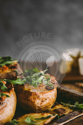 Close up of baked stuffed potatoes with cheese, vegetables, sour cream and rucola on wooden table. Rustic background. Copy space