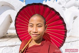 Portrait of young novice monk with umbrella, Burma