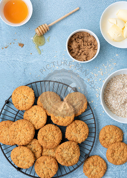 Homemade honey and oatmeal biscuits on a wire rack with bowls of ingredients.