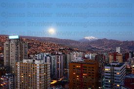 Full moon rising over central La Paz and Mt Illimani , Bolivia