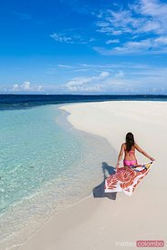 Woman with sarong walking on a beach, Maldives