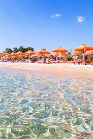 Beach with orange parasols in summer. Kefalonia, Greek Islands, Greece