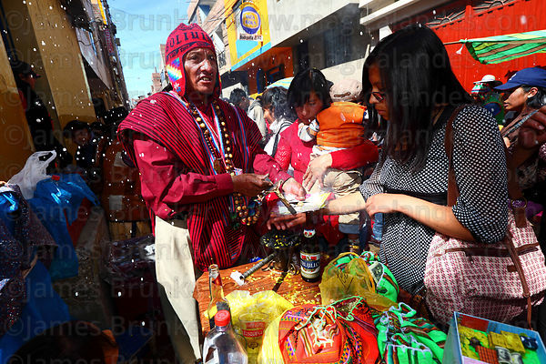 Aymara shaman blessing miniature college degree certificates with crucifix at Alasitas festival, Puno, Peru