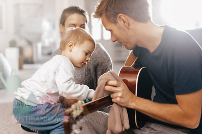 Little girl examining father's guitar at home