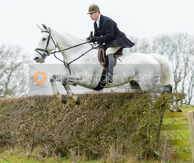 Angus Smales jumping a hedge at Wilson's - The Cottesmore Hunt at Manor Farm