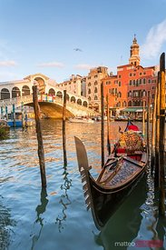 Rialto bridge at sunset and gondola, Venice, Italy