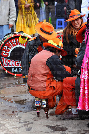 Man sitting on 2 inverted beer bottles at street party after formal parades, Virgen de la Candelaria festival, Puno, Peru