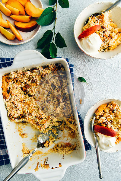 Peach cobbler in a rectangular baking pan and in two white ceramic bowls topped with vanilla ice cream and peach slices photographed from top view. Peach slices on a separate plate and green leaves accompany.