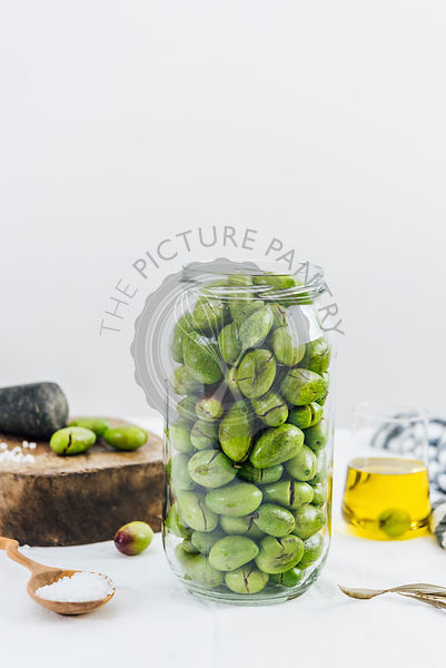 Green olives in a glass jar to be brined photographed from front view. A glass cup of olive oil and a wooden mallet accompany.