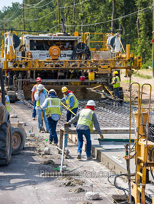 Highway construction workers prepare a rebar grid for freshly poured concrete on a stretch of road